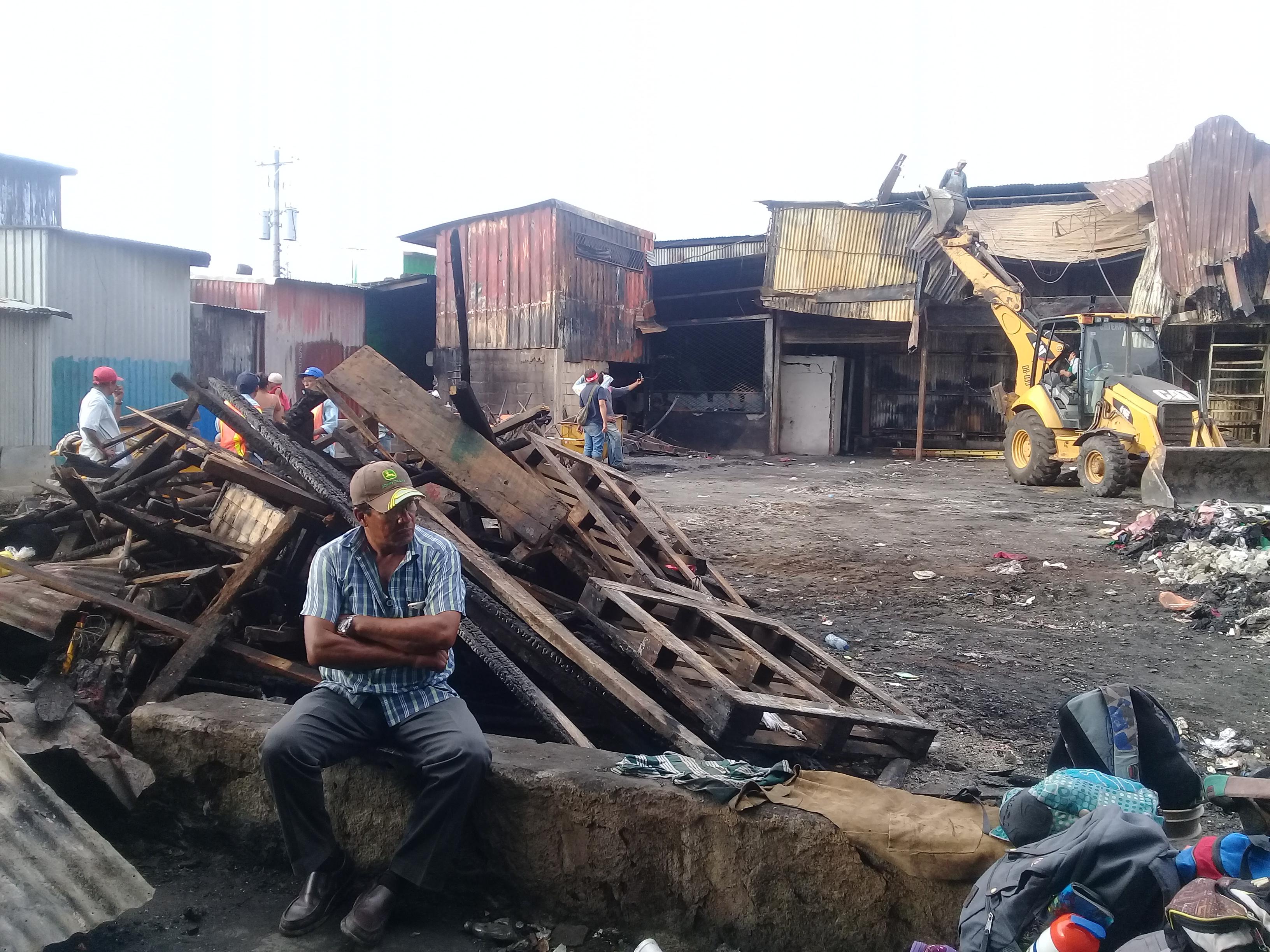 Comerciante que perdió todo observa como trabajan en los escombros. Fotografía: Artículo 66