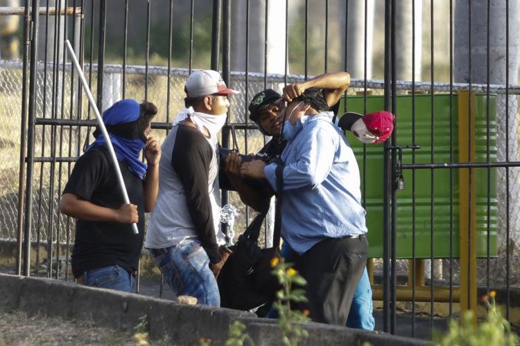 Momento en que turbas orteguistas le quitan la cámara a foto periodista Uriel Molina. Foto: Cortesía/La Prensa