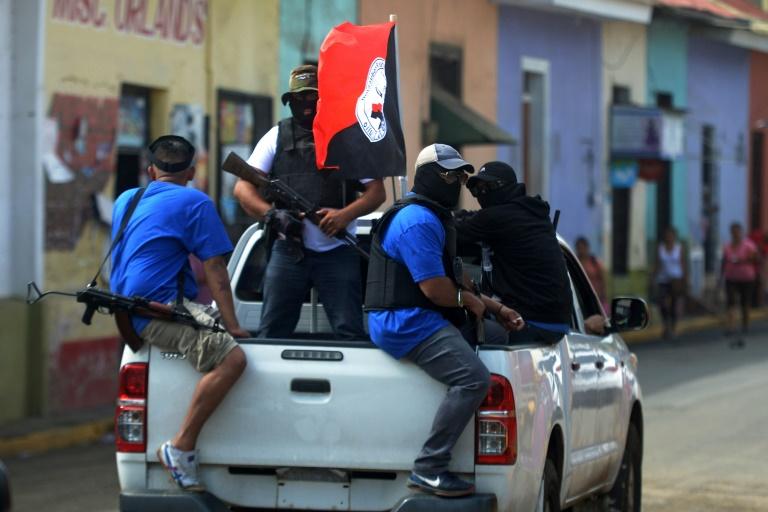 Paramilitares, encapuchados, armados y con la bandera del FSLN, tras el levantamiento de tranques en la ciudad de Masaya. Foto: AFP