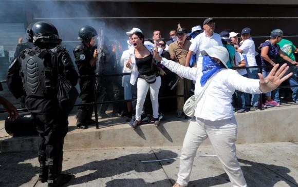 Policía reprimiendo a manifestantes azul y blanco. Foto: tomada de El Colombiano