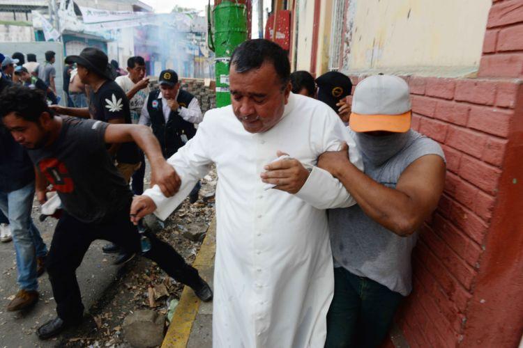 El padre César Augusto Gutiérrez, de la iglesia de San Sebastian de Monimbó, cuando fue agredido por la Policía mientras estos intentaban interferir para detener represión. Foto: Cortesía Manuel Esquivel/La Prensa