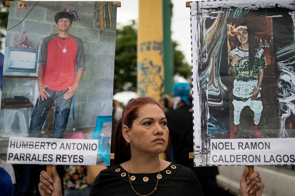 Iris Lagos sostiene los carteles con las fotos de su esposo e hijos asesinados. Foto: Franklin Villavicencio | Confidencial