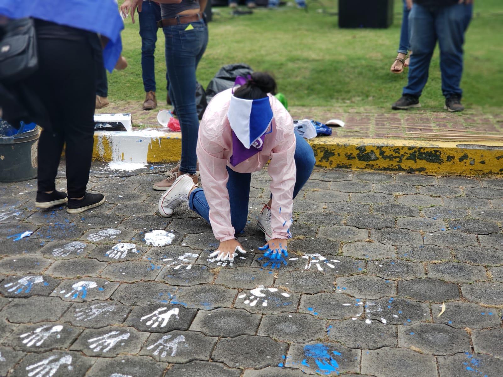 Universitarias mancharon sus manos de pintura azul y blanco y plasmaron sus manos en el adoquinado y portón del recinto. Foto: G. Shiffman / Artículo 66