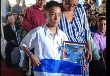 """Hijo de """"Chabelo"""" subió a recibir su diploma de sexto grado con la bandera de Nicaragua y con el retrato de su padre"""