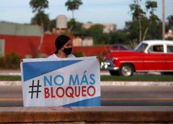 Fotografía del 20 de junio que muestra a una mujer que sostiene un cartel, durante la regata parte de una campaña contra el bloqueo de Estados Unidos a la isla, en la bahía de Matanzas (Cuba). EFE/Yander Zamora